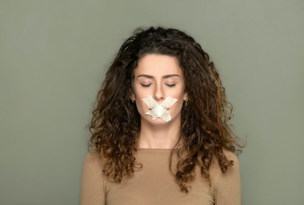 Young woman with closed eyes and taped lips