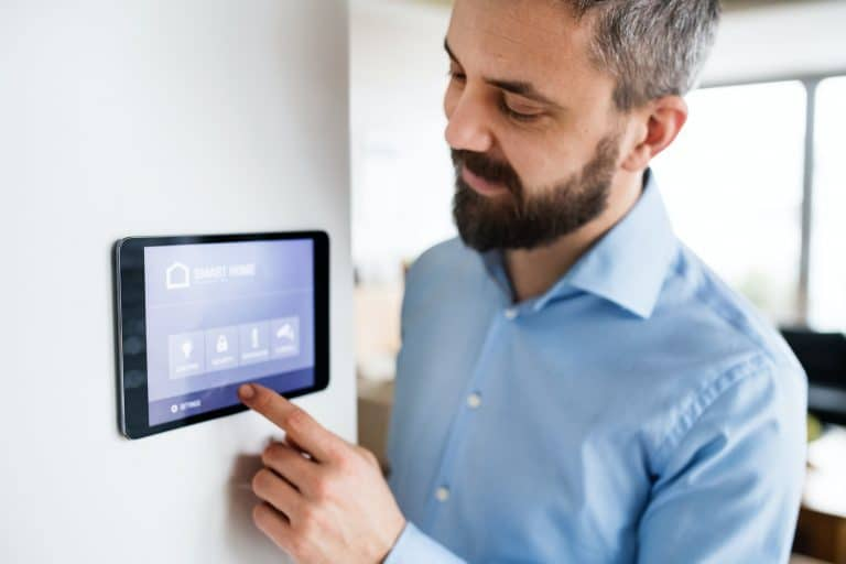 A man pointing to a tablet with smart home screen at home.